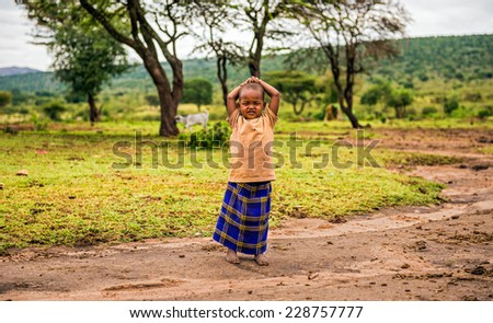 MAASAI MARA, KENYA - OCTOBER 17, 2014 : Young african girl posing in a Masai tribe village. The Maasai are a Nilotic ethnic group living in southern Kenya and northern Tanzania