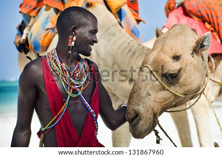 Maasai sitting by the ocean on the beach - stock photo
