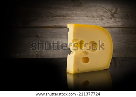 Maasdam cheese on wooden background - stock photo