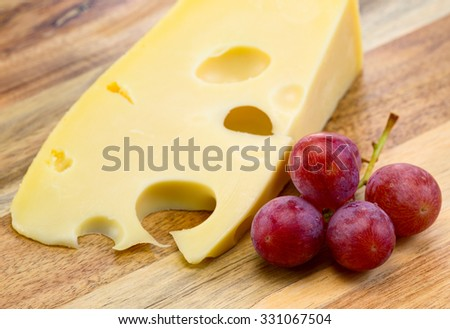 Maasdam cheese with grapes on the wooden board. - stock photo