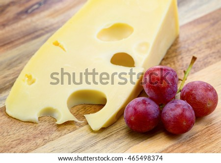 Maasdam cheese with grapes on the wooden board.