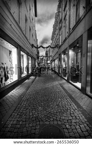 MAASTRICHT, NETHERLANDS - JANUARY 09, 2015: Old narrow street in the historic center. Black and white. Vignetting. Maastricht is the oldest city of the Netherlands.