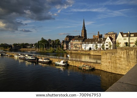 Maastricht, the Dutch city on the river Maas with boats in the harbor and the Sint Martinuskerk church in the old town, Netherlands, Europe