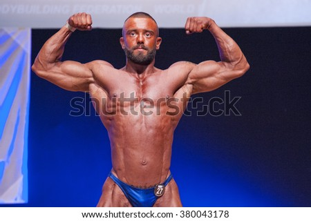MAASTRICHT, THE NETHERLANDS - OCTOBER 25, 2015: Male bodybuilder Dennis Theys flexes his muscles and shows his best front double biceps pose at the World Grandprix Bodybuilding and Fitness