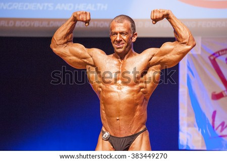 MAASTRICHT, THE NETHERLANDS - OCTOBER 25, 2015: Male bodybuilder flexes his muscles and shows his best physique in a front double biceps  pose on stage at the World Grandprix Bodybuilding and Fitness