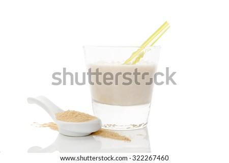 Maca powder on spoon and maca milkshake in glass isolated on white background. Natural alternative medicine. - stock photo