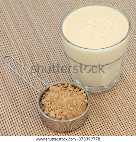 Maca root powder and drink in a glass over bamboo. Health and body building food. - stock photo