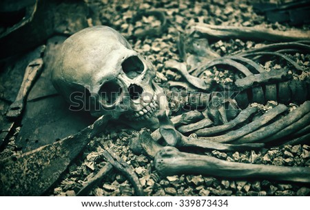 Macabre open grave with a human skeleton in a catacomb or burial site suitable as a Halloween or horror background - stock photo