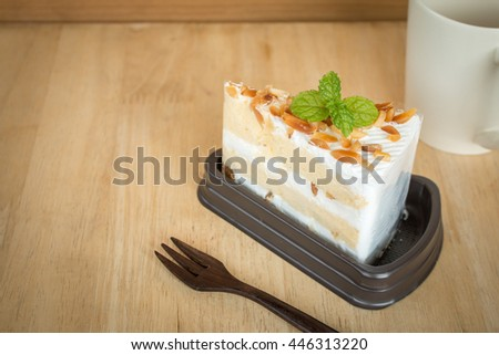 Macadamia cake with Plastic wraps in package on wooden table background.