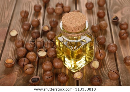 Macadamia nut oil on a brown background - stock photo