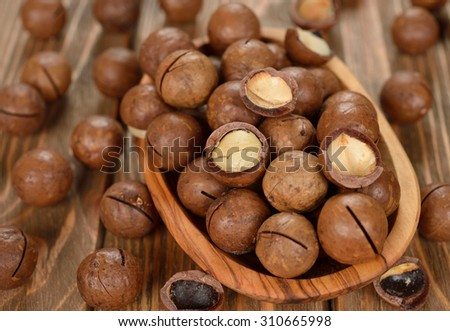 Macadamia nuts in a wooden bowl on a brown background