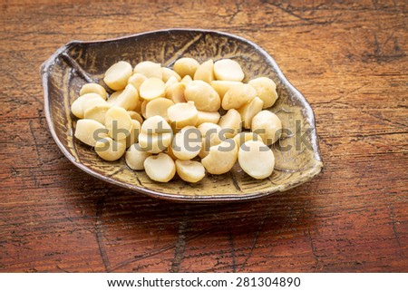 macadamia nuts on a ceramic leafs shaped bowl against rustic wood - stock photo