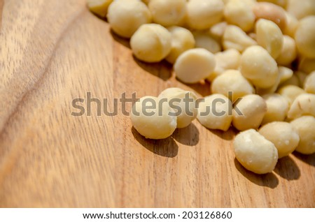 Macadamia nuts spilled out onto a wooden table - stock photo