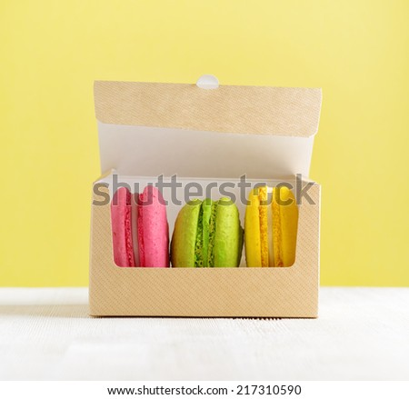 Macaron box on white wooden table. - stock photo