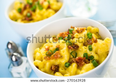Macaroni and cheese garnished with bacon bits and chives. - stock photo