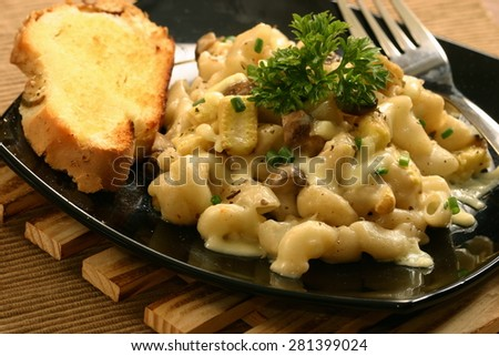 Macaroni and cheese served with bread - stock photo