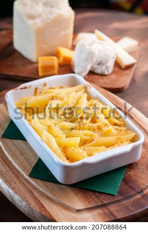 Macaroni cheese in white tray on wooden plate - stock photo