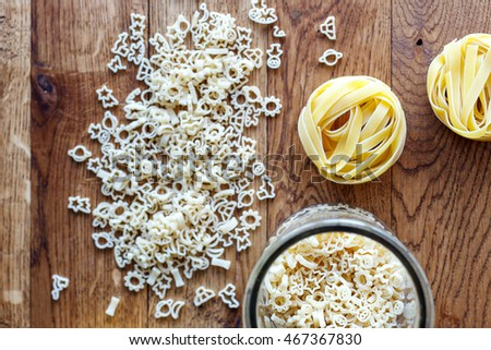 macaroni  on  old wooden table. Focus on macaroni at the bottle
