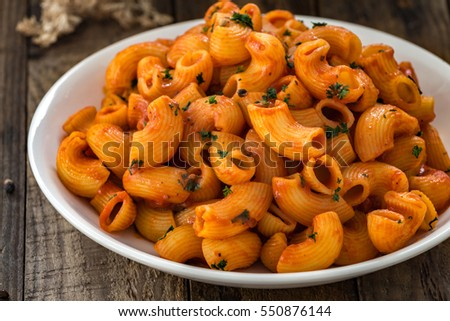 macaroni pasta in tomato spicy sauce with wood on a wooden table