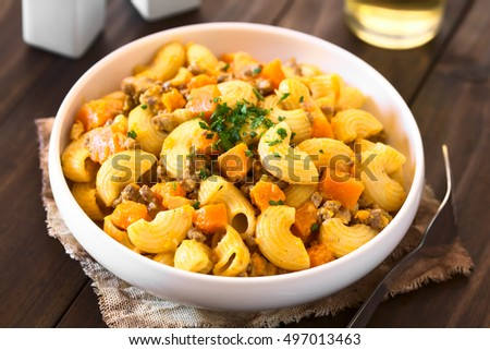 Macaroni pasta with creamy pumpkin and mincemeat sauce garnished with parsley served in white bowl, photographed with natural light (Selective Focus, Focus in the middle of the dish)