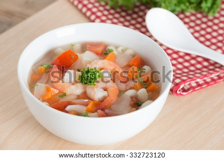 Macaroni with shrimp soup on white bowl.