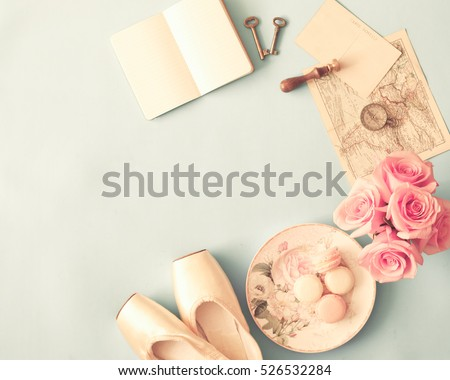 Macarons in a plate, roses, map, compass, postcard, skeleton keys, notebook and ballet shoes