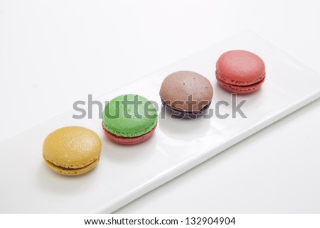 macarons in dish on pink table - stock photo