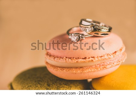 macarons with wedding rings close up shot, retro filter - stock photo