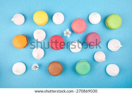 macaroon background, colorful macaroons with flower on blue background - stock photo