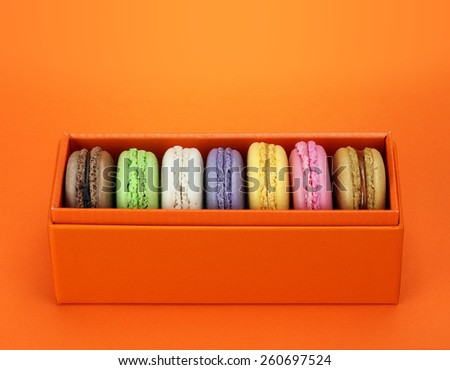 Macaroon in the orange box on orange background. Dessert - stock photo