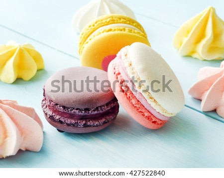 Macaroons and meringues on blue background. Shallow dof. - stock photo