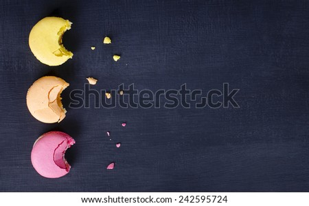Macaroons background, colorful cookies on black wooden table - stock photo