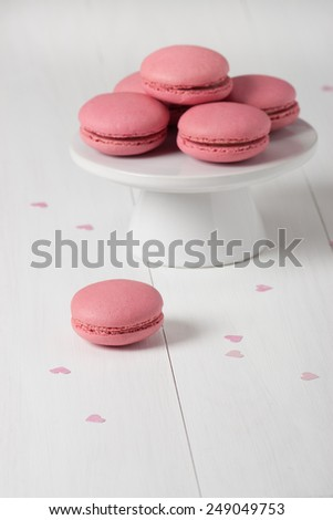 Macaroons Biscuits On White Stand. Paper Hearts.