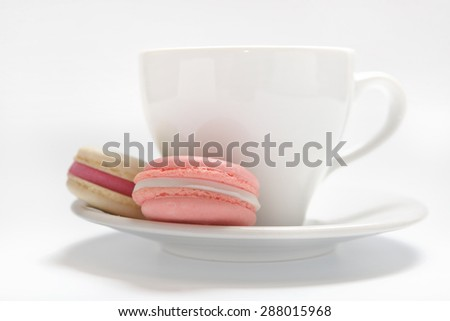macaroons cookies and tea cup on a white background with a small depth of field - stock photo