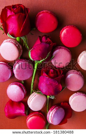 Macaroons on a red background of roses and one light - stock photo