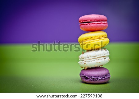 Macaroons on green kitchen surface - stock photo