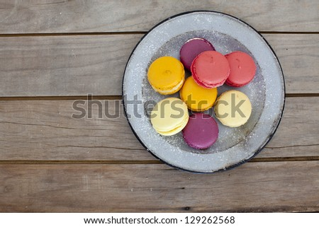 macaroons on vintage plate and rustic table - stock photo