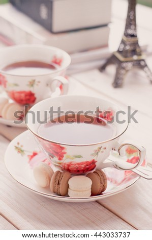 macaroons with cup of tea on wooden background