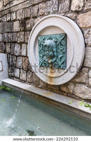 MACAU, CHINA - OCTOBER 15, 2014 - Water fountain and spout at Lilau Square. They believe if we throw coin to it, we will come back to Macau again.