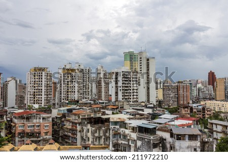 MACAU - JUNE 6, 2014: Macau packed houses and city skyline under the cloudy sky. Rich and poor stays close to each other in Macau, China.