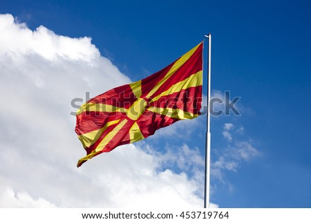 Macedonian flag waving on blue and white sky, on the mast. Sunny day, clouds in background.