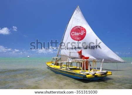 MACEIO, BRAZIL - OCTOBER 10, 2015: Traditional jangada boats providing visits to nearby reefs are often sponsored by large companies such as Claro, a popular celular phone company in Brazil. - stock photo