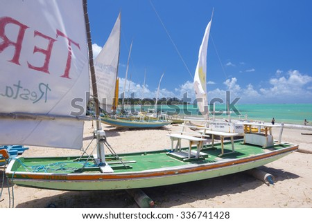 MACEIO, BRAZIL - OCTOBER 10, 2015: Traditional jangada fishing boats are parked on a sandy beach under the hot sun of Brazil's northeast coast in Maceio, Alagoas - stock photo