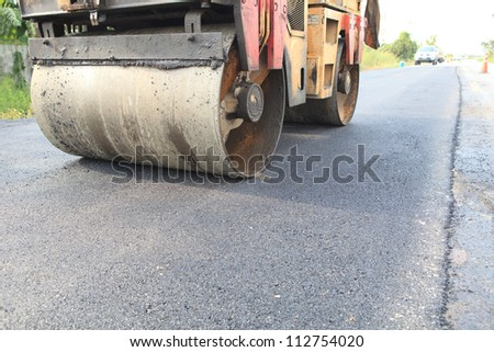 machine and worker at road construction - stock photo