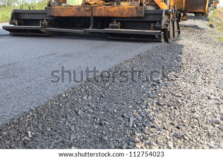 machine and worker at road construction