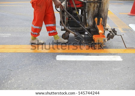 machine and worker at road construction use for road and traffic sign painting  - stock photo