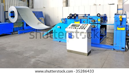 machine for rolling steel sheet in warehouse - stock photo