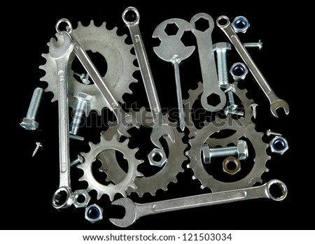 Machine gear, metal cogwheels, nuts and bolts isolated on black - stock photo