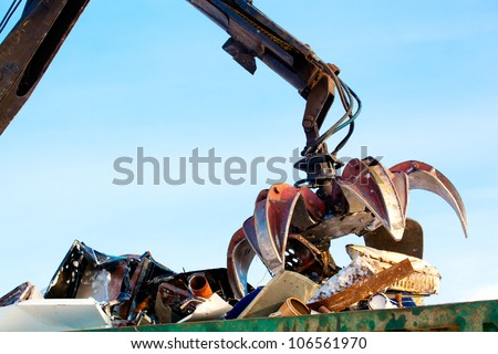 machine loader manipulator with hydraulic multivalve crab bucket uploads waste steel into a truck - stock photo