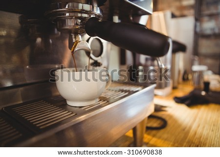 Machine making a cup of coffee in a cafe - stock photo